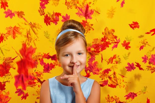 Mała dziewczynka w stroju księżniczki z opadających liści jesienią