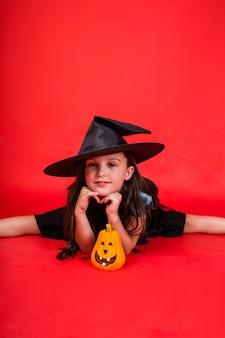 Mała dziewczynka w stroju wiedźmy siedzi z dynią na czerwonym tle z kopią przestrzeni