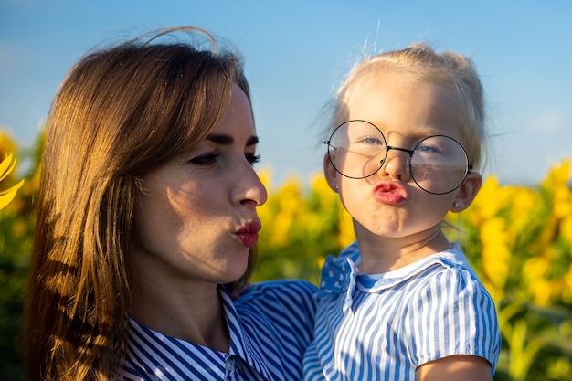 Mała dziewczynka w sukience i okularach w ramionach matki na słonecznikowym polu.