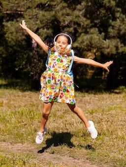 Mała dziewczynka w sukience i słuchawkach bawi się i skacze w parku na trawie.