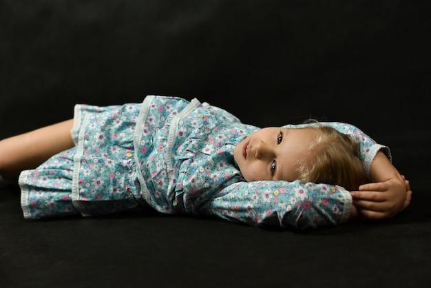 Mała dziewczynka w sukience kłamie i marzy