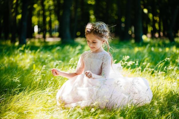 Mała dziewczynka w sukience siedzi na trawie