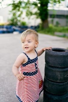 Mała dziewczynka w sukience stoi obok stosu małych opon na parkingu samochodowym