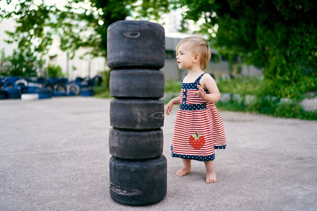 Mała dziewczynka w sukience stoi w pobliżu małych opon