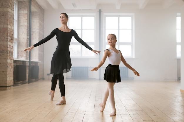 Mała dziewczynka w sukience tutu uczy się tańczyć balet razem z młodą kobietą w studiu tańca
