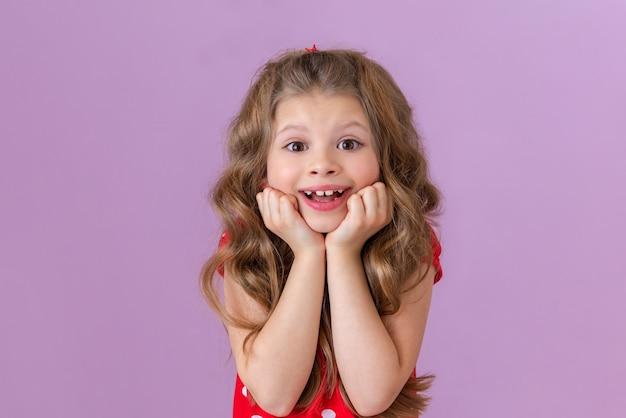 Mała dziewczynka w sukience w kropki i kręconych włosach wygląda na bardzo zaskoczoną i szczęśliwą.
