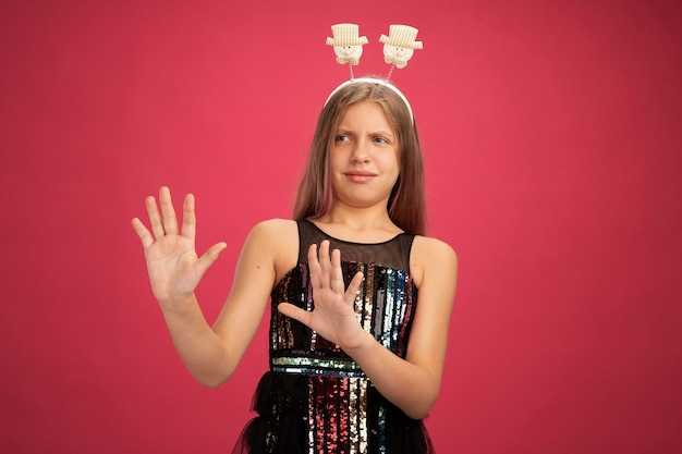 Mała dziewczynka w sukience z brokatem i zabawnym pałąku patrząc na bok, martwiąc się, trzymając się za ręce, koncepcja święta nowego roku stojąca na różowym tle