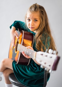 Mała dziewczynka w sukni bawić się gitarę akustyczną