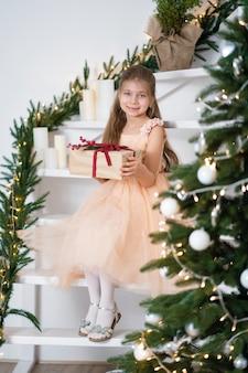 Mała dziewczynka w sukni księżniczki obchodzi boże narodzenie. świąteczna bajka magiczna. szczęśliwe dzieciństwo.