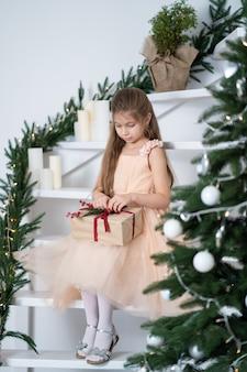 Mała dziewczynka w sukni księżniczki obchodzi boże narodzenie
