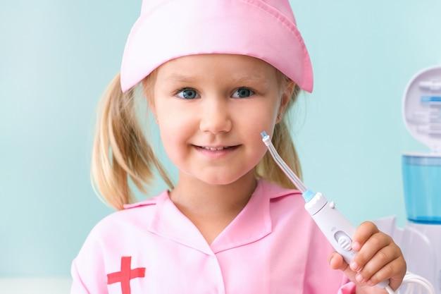 Mała dziewczynka w sukni pielęgniarki myje zęby za pomocą irygatora. dziewczyna myje zęby strumieniem wody z irygatora.