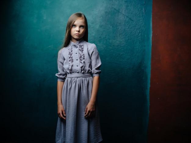 Mała dziewczynka w sukni pozowanie studio na białym tle