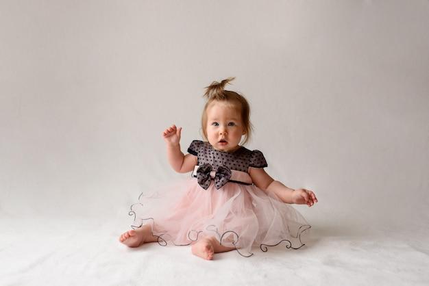 Mała dziewczynka w sukni siedzi na białej powierzchni