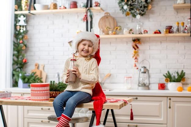 Mała dziewczynka w swetrze i czapce mikołaja pije mleko kakaowe na kuchennym stole.