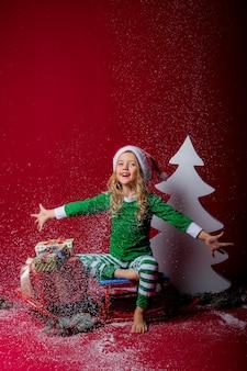 Mała dziewczynka w świątecznej piżamie lub kostiumie elfa i czapce mikołaja łapie śnieg siedząc na sankach
