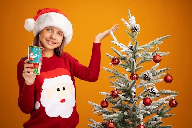 Mała dziewczynka w świątecznym swetrze i mikołajowym kapeluszu trzymająca kolorowy papierowy kubek przedstawiająca ramieniem dłoni uśmiechnięta stojąca obok choinki na pomarańczowym tle