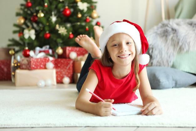 Mała dziewczynka w świątecznym wnętrzu pisze list do świętego mikołaja