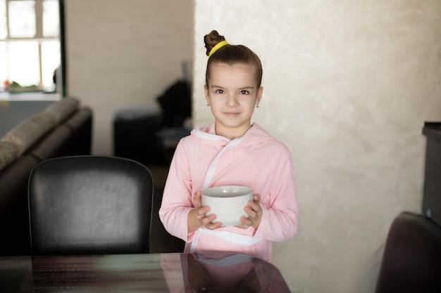 Mała dziewczynka w szacie trzyma talerz w dłoniach i ma zamiar zjeść śniadanie.