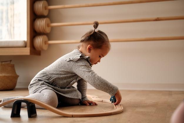 Mała dziewczynka w szarej sukience bawi się w dziecięcym pokoju kolejką drewnianą i pociągiem, którym on jest