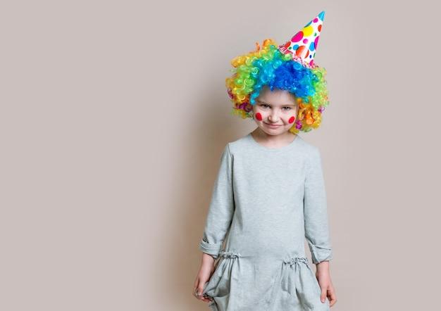 Mała dziewczynka w szarej sukience i kolorowej peruce