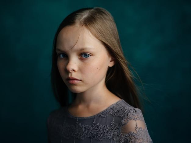 Mała dziewczynka w szarej sukience na zielonym tle bliska przycięty widok. wysokiej jakości zdjęcie