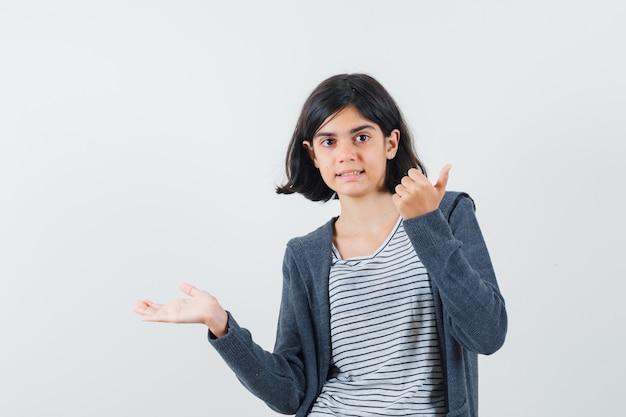 Mała dziewczynka w t-shircie, marynarce, rozłożona na bok, pokazująca kciuk do góry i wyglądająca na pewną siebie