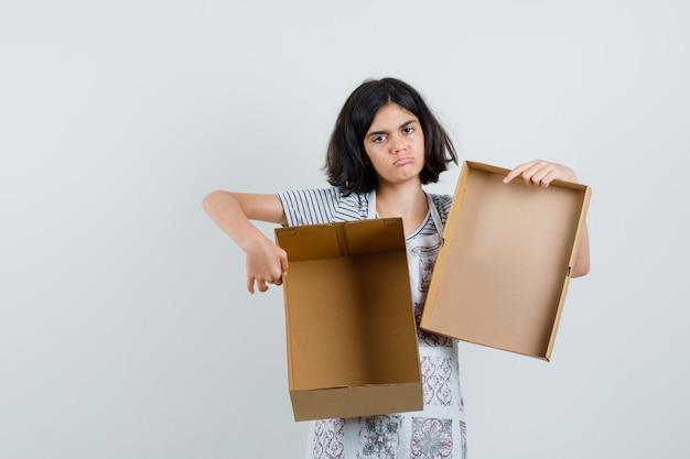 Mała dziewczynka w t-shircie, w fartuchu trzymająca puste kartonowe pudełko i spoglądająca w dół,