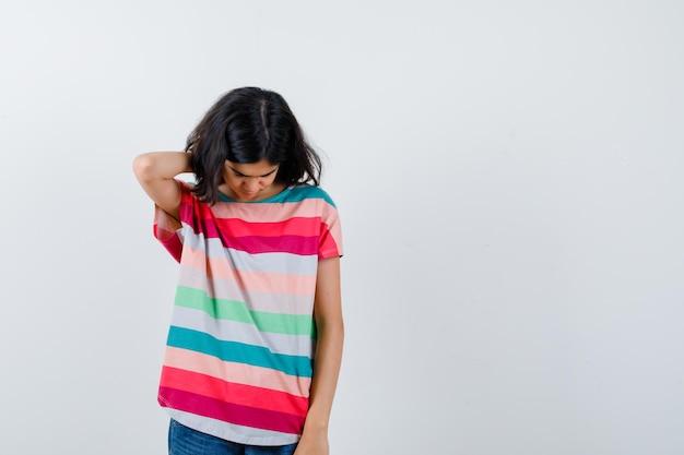 Mała dziewczynka w t-shirt drapiąc się po głowie i patrząc zdenerwowany, widok z przodu.