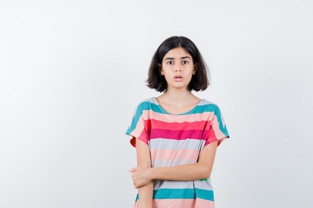 Mała dziewczynka w t-shirt, dżinsy, trzymając rękę na ramieniu i patrząc zaskoczony, widok z przodu.