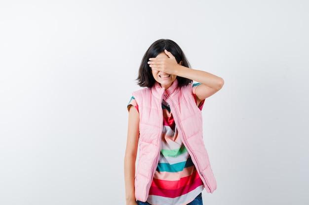 Mała dziewczynka w t-shirt, kamizelka puchowa, dżinsy zakrywające oczy ręką i wyglądająca na przestraszoną, widok z przodu.