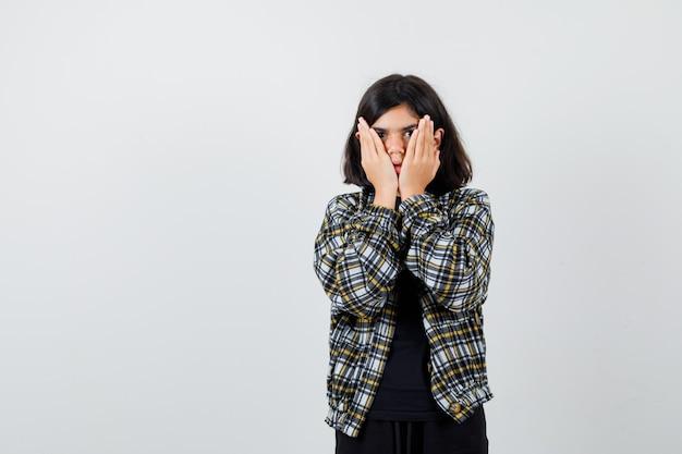 Mała dziewczynka w t-shirt, kurtka, trzymając się za ręce na policzkach i patrząc przestraszony, widok z przodu.