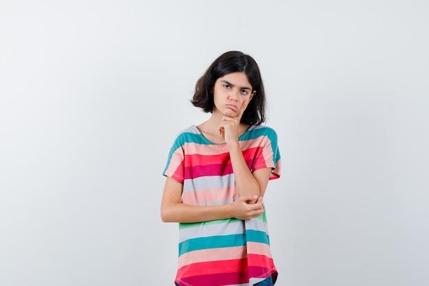 Mała dziewczynka w t-shirt podpierając podbródek pod ręką i patrząc smutny, widok z przodu.