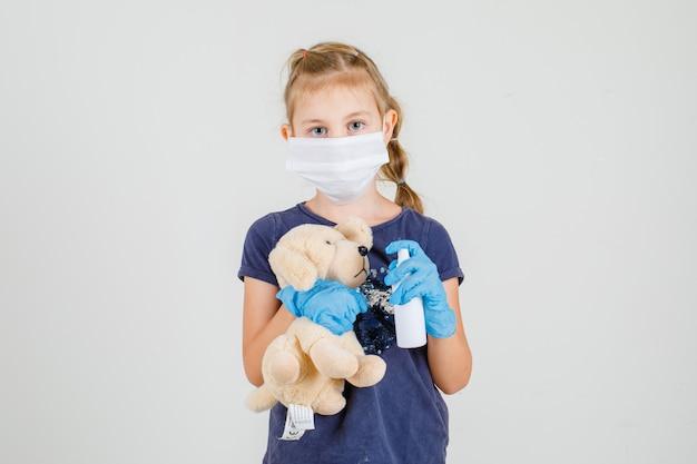 Mała dziewczynka w t-shirt, rękawiczki i maskę medyczną desenfecting niedźwiedź zabawka, widok z przodu.