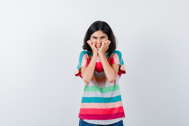 Mała dziewczynka w t-shirt, trzymając się za ręce na policzkach i patrząc szczęśliwy, widok z przodu.