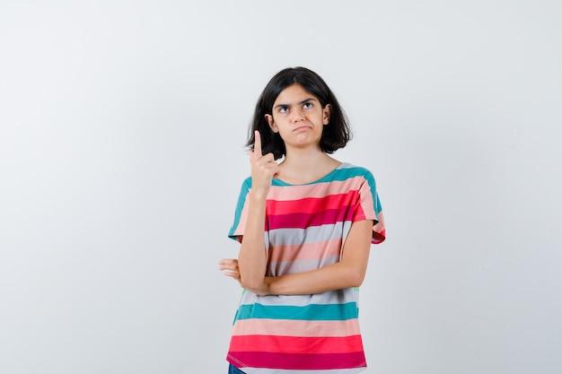 Mała dziewczynka w t-shirt, wskazując w górę i patrząc zamyślony, widok z przodu.