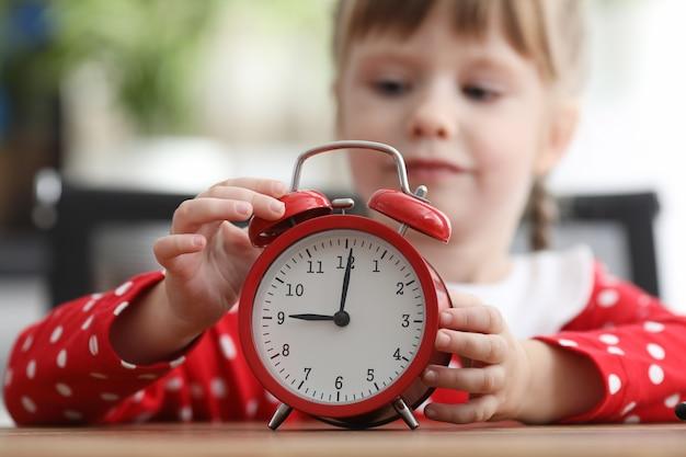 Mała dziewczynka w tle naciska przycisk czerwonego budzika ręką w godzinach porannych