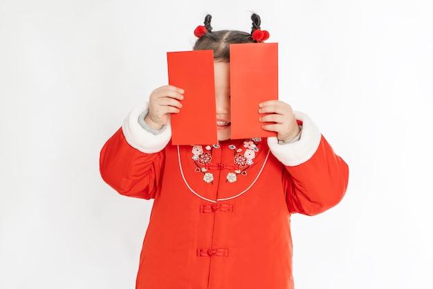 Mała dziewczynka w tradycyjnym chińskim stroju trzyma w dłoni czerwoną kopertę noworoczną