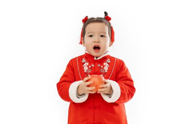 Mała dziewczynka w tradycyjnym chińskim stroju trzyma w ręku jabłko