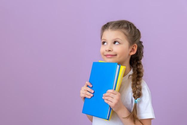Mała dziewczynka w warkoczykach i książka w jej rękach na fioletowym tle