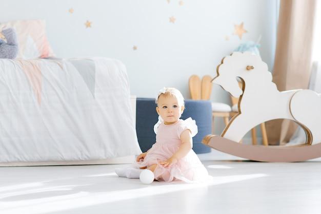 Mała dziewczynka w wieku 1 roku w różowej sukience siedzi na podłodze w pokoju dziecięcym