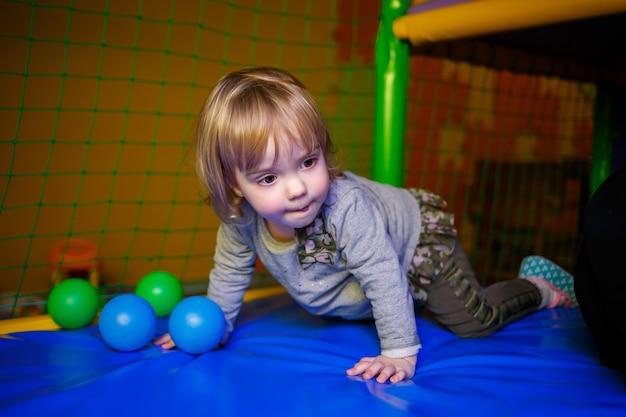 Mała dziewczynka w wieku 2 lat bawi się w strefie dla dzieci z atrakcjami