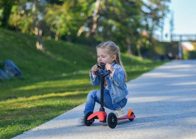 Mała dziewczynka w wieku 3 lat jeździ na hulajnodze