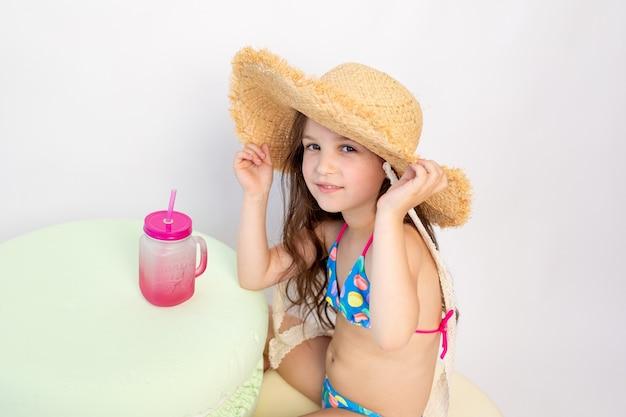 Mała dziewczynka w wieku 5-6 lat siedzi w kostiumie kąpielowym z koktajlem na białym tle odizolowane, miejsce na tekst
