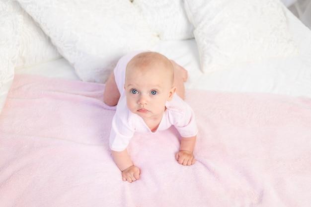 Mała dziewczynka w wieku 6 miesięcy czołganie się na białym i różowym łóżku w domu, odwracając wzrok, widok z góry