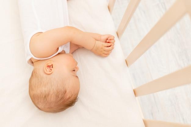 Mała dziewczynka w wieku 6 miesięcy śpi w białym łóżku, zdrowy sen dziecka