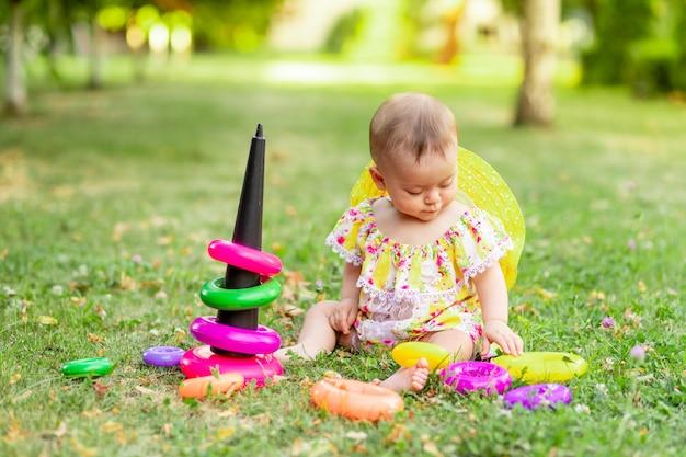 Mała dziewczynka w wieku 7 miesięcy siedzi na zielonej trawie w żółtej sukience i kapeluszu i bawi się piramidą, wczesny rozwój dzieci do roku, spacery na świeżym powietrzu