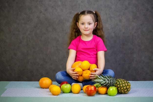 Mała dziewczynka w wieku sześciu lat bardzo kocha owoce. witaminy i zdrowe odżywianie.