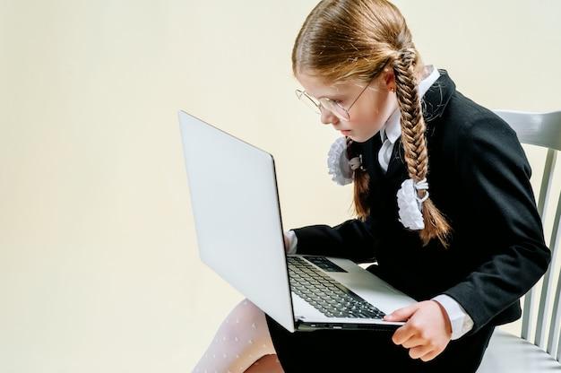 Mała dziewczynka w wieku szkolnym wygląda w laptopie na jasnym tle, uzależnienie od internetu