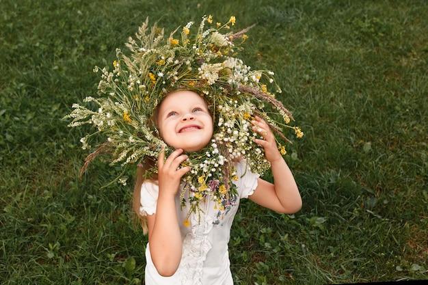 Mała dziewczynka w wieńcu z polnych kwiatów patrzy w górę i śmieje się