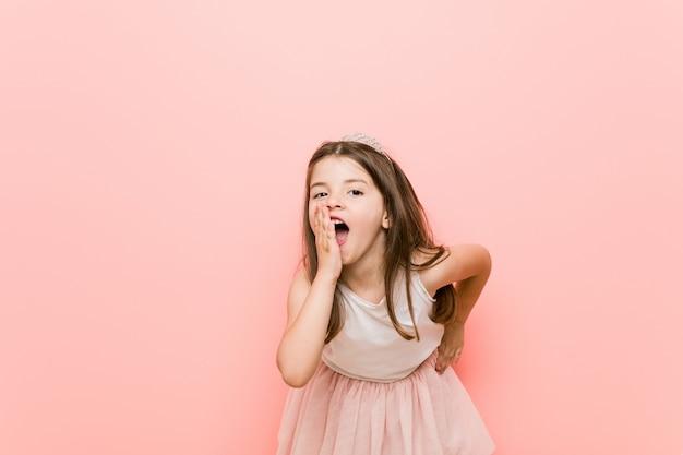 Mała dziewczynka w wyglądzie księżniczki mówi sekret